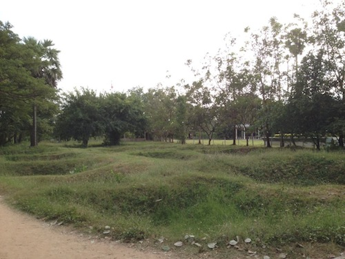Mass graves at Choeung Ek where large number of bodies are still buried so shallow that bones and clothing surface after heavy rainfalls even till today