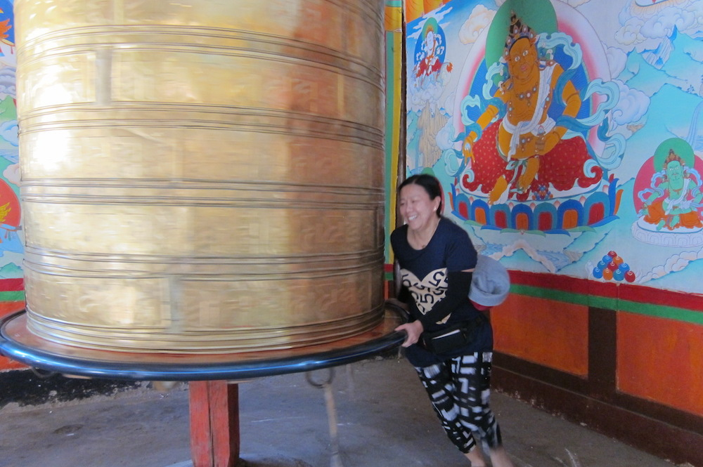 My mom spinning a Tibetan prayer wheel - remember to do it three rounds (hear the bell ring thrice) and in a clockwise direction