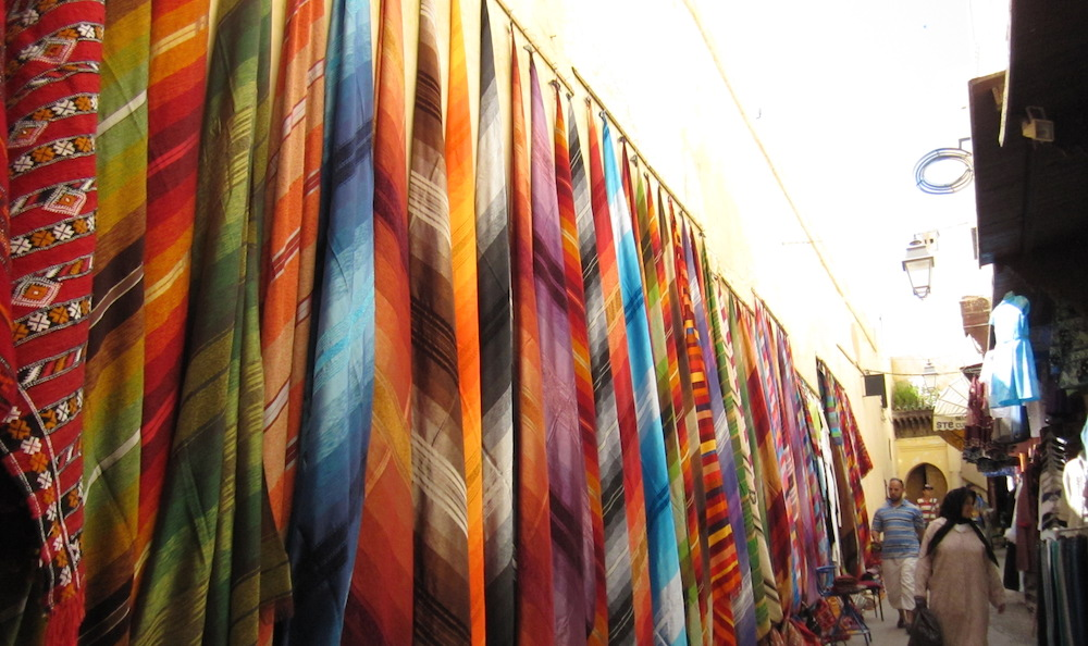Handwoven silk scarves draped against the age-old city walls